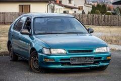 Carro japonês azul abandonado do carro com porta traseira dos azuis celestes com um pneu liso Foto de Stock