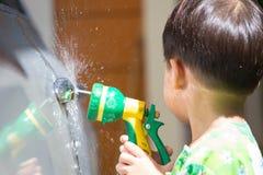Carro lavado menino pelo pulverizador de água Fotos de Stock Royalty Free