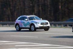 Carro luxuoso Infiniti que apressa-se na estrada vazia Imagem de Stock Royalty Free