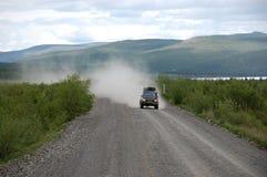Carro na estrada de Kolyma da estrada do cascalho no interior do russo Fotografia de Stock