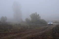 Carro na estrada de terra no dia nevoento fotos de stock
