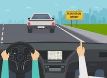 Carro na opinião da estrada do interior As mãos do motorista no volante, sinal de aviso retardam por favor drively Imagem de Stock Royalty Free