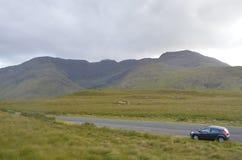 Carro no meio de uma estrada nacional com vegetação e montanhas na Irlanda Foto de Stock Royalty Free