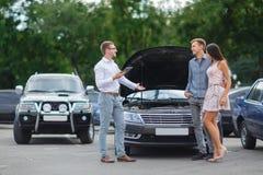 Carro novo de exploração Escolha o automóvel novo Proprietário futuro do carro de motor Carro usado de compra na loja Família da  foto de stock royalty free