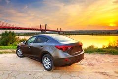 Carro novo no por do sol Imagens de Stock Royalty Free