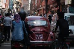 Carro oval vermelho velho Thamel aglomerado cruzamento Stree de Volkswagen Beetle Foto de Stock