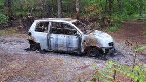 Carro para fora queimado roubado abandonado perto da madeira da floresta Fotos de Stock Royalty Free