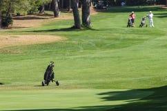 Carro para traer a los clubs de golf en el campo de golf del ver Imágenes de archivo libres de regalías