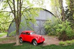 Carro pequeno retro vermelho do vintage que está no jardim no verão Foto de Stock Royalty Free