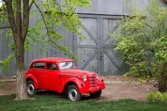 Carro pequeno retro vermelho do vintage que está no jardim no verão Fotografia de Stock Royalty Free