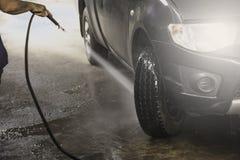 Carro preto de lavagem pela água de alta pressão Máquina limpa de Washington do carro, lavagem de carro com esponja e mangueira Imagem de Stock Royalty Free