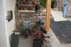 Carro que cultiva un huerto con la maceta en el jardín de flores, carretilla por completo de hojas secadas, cultivando un huerto  Fotos de archivo libres de regalías