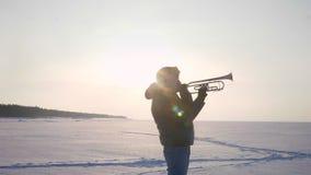 Carro que enfoca hacia fuera tirado solamente de músico caucásico en el perfil que toca la trompeta en sol en fondo congelado de  almacen de metraje de vídeo