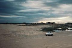 carro 4x4 que espera ao lado de uma lagoa na frente das dunas de areia no por do sol com céu bonito fotografia de stock royalty free