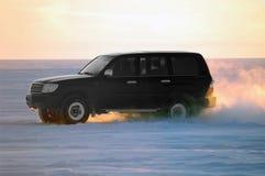Carro que um veículo através dos campos monta em um lago snow-bound fotos de stock royalty free