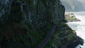 Carro que vai perto do mar ao longo das inclinações de montanha Tiro aéreo de Madeira vídeos de arquivo