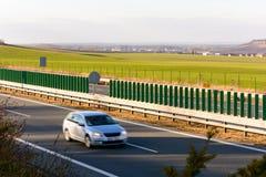 Carro que viaja na estrada no por do sol Imagens de Stock