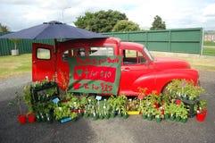 Carro retro vermelho no mercado Imagens de Stock Royalty Free