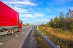 Carro rojo que mueve encendido una carretera Foto de archivo libre de regalías