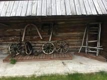 Carro rural do camponês do russo antigo do vintage na jarda de uma casa de madeira Imagens de Stock Royalty Free