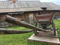 Carro rural do camponês do russo antigo do vintage na jarda de uma casa de madeira Fotos de Stock