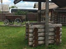 Carro rural do camponês do russo antigo do vintage na jarda de uma casa de madeira Fotografia de Stock Royalty Free