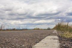 Carro só que viaja para baixo pelos prados verdes Fotografia de Stock