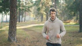 Carro tirado de hombre barbudo apuesto con los auriculares que corren en parque y que escuchan la música en día soleado del otoño metrajes
