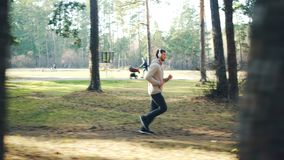 Carro tirado de hombre joven barbudo en chándal y de las zapatillas de deporte que activan en parque y que escuchan la música con almacen de metraje de vídeo
