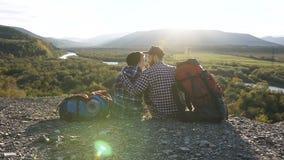 Carro tirado de los pares felices lindos que se sientan en la tierra durante viajar en la montaña almacen de video