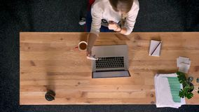 Carro tirado del top abajo de la opinión la mujer ocasional-vestida que habla en videochat usando smartphone en oficina delante d almacen de video