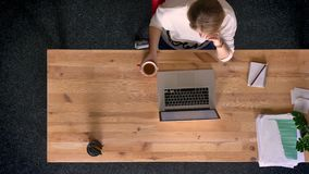 Carro tirado del top abajo de la opinión la mujer ocasional-vestida que mira en la pantalla del ordenador portátil, café de consu almacen de video