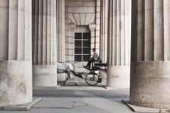 Carro traído por caballo que pasa a través del collonnade Imágenes de archivo libres de regalías