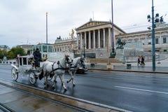 Carro tradicional del caballo en Ringstrasse y el austriaco Parliamen fotos de archivo