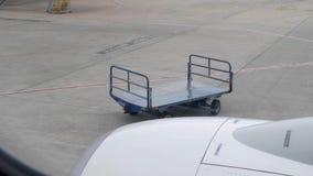 Carro vacío del equipaje en el aeropuerto Visión desde el avión a través de la ventana