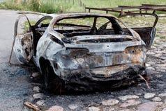 Carro velho para fora oxidado queimado perto da estrada Fotos de Stock