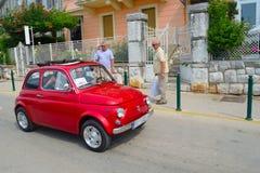 Carro vermelho clássico do motor 500 de Fiat que está sendo conduzido ao longo da rua Fotografia de Stock
