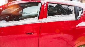 Carro vermelho coberto de neve fotografia de stock
