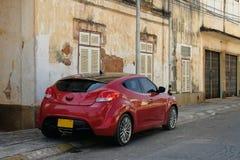 Carro vermelho contra a construção velha Fotos de Stock Royalty Free
