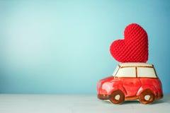 Carro vermelho diminuto que leva um coração vermelho fotos de stock royalty free