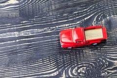 Carro vermelho do recolhimento no fundo de madeira escuro imagens de stock
