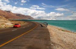 Carro vermelho em uma estrada. imagens de stock