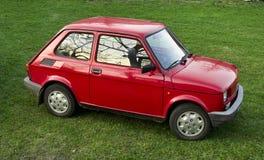 Carro vermelho estacionado na grama Imagens de Stock Royalty Free
