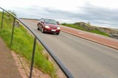 Carro vermelho que apressa-se na rua Fotos de Stock Royalty Free