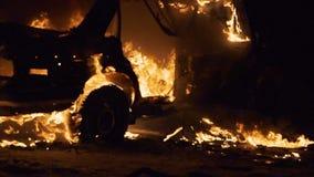 Carrocería ardiendo del backgroung de la falta de definición, coche quebrado en el fuego almacen de metraje de vídeo
