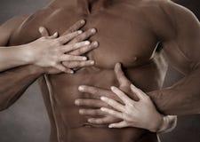 Carrocería masculina muscular Manos femeninas foto de archivo libre de regalías