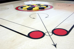 Carrom board with striker and coins Stock Images