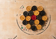 Carrom men pieces arranged on a board. Black and white carrom men arranged on a carrom board waiting for a match. This is an indian origin game very popular in Royalty Free Stock Image