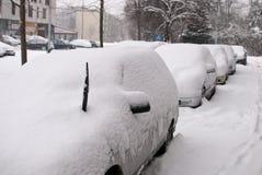 Carros cobertos com a neve em um parque de estacionamento Imagem de Stock Royalty Free