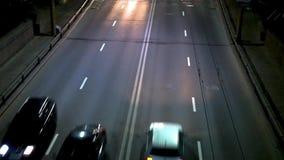 Carros com os faróis em para ir rapidamente na estrada sobre a ponte na noite Vista para baixo no tráfego video estoque